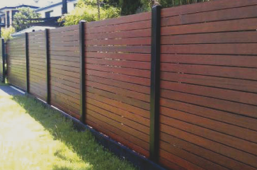 beautiful-wood-fence-with-horizontal-wood-and-stained-beautifully-with-different-colored-fence-posts-adding-privacy-to-a-residence