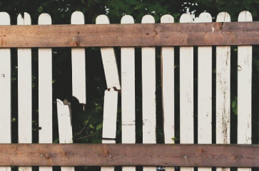 broken-fence-in-need-of-fence-repair.-white-fence-pickets-on-two-rails